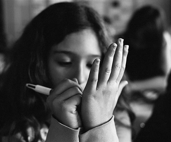 Une élève de sixième écrit dans sa main, cité scolaire Jean-Jaurès, Montreuil, 2010