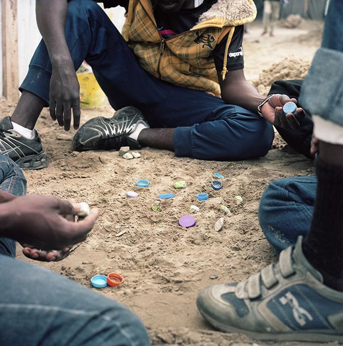 Des jeunes Soudanais jouent au jeu du dalla, Jungle de Calais, 9 mai 2016