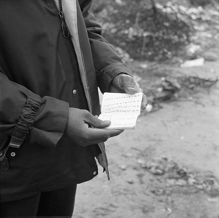 Un homme nommé Abdou me présente son carnet de français  sur le chemin de l'école laïque du chemin des Dunes, Jungle de Calais, 7 mars 2016