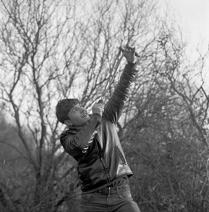 Un garçon tire au lance-pierre pour la photographie, Jungle de Calais, 2016